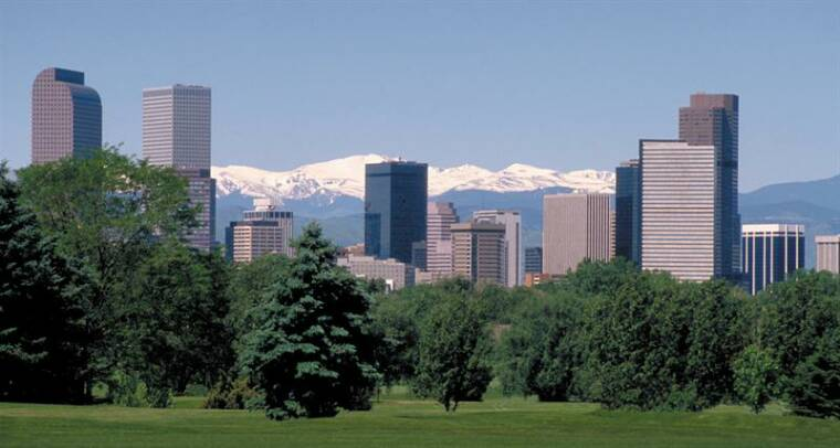 snowcapped mountains behind denver downtown skyline